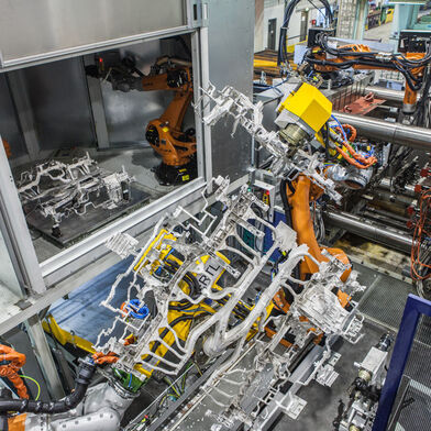 A dashboard support made from magnesium by pressure die-casting is being passed by a robot to a downstream work station (on the right in the background the 4000 tons pressure die-casting machine)